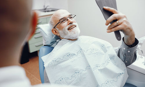 old man smiling after dentures
